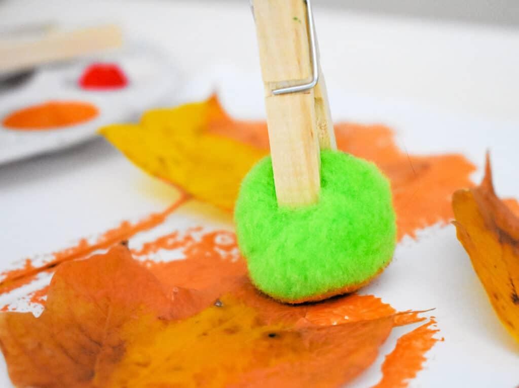 Pom Pom Painting an outline of a leaf