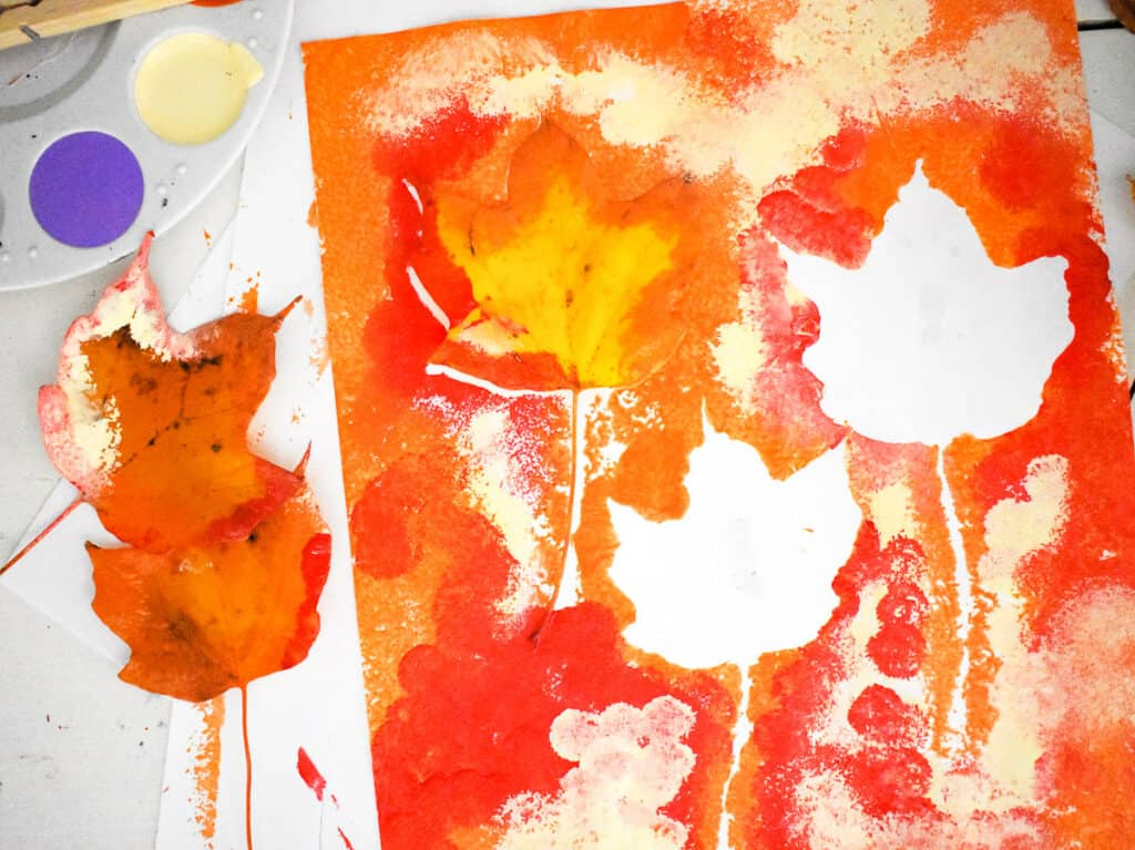 Removing a few leaves from fall leaf pom pom painting activity
