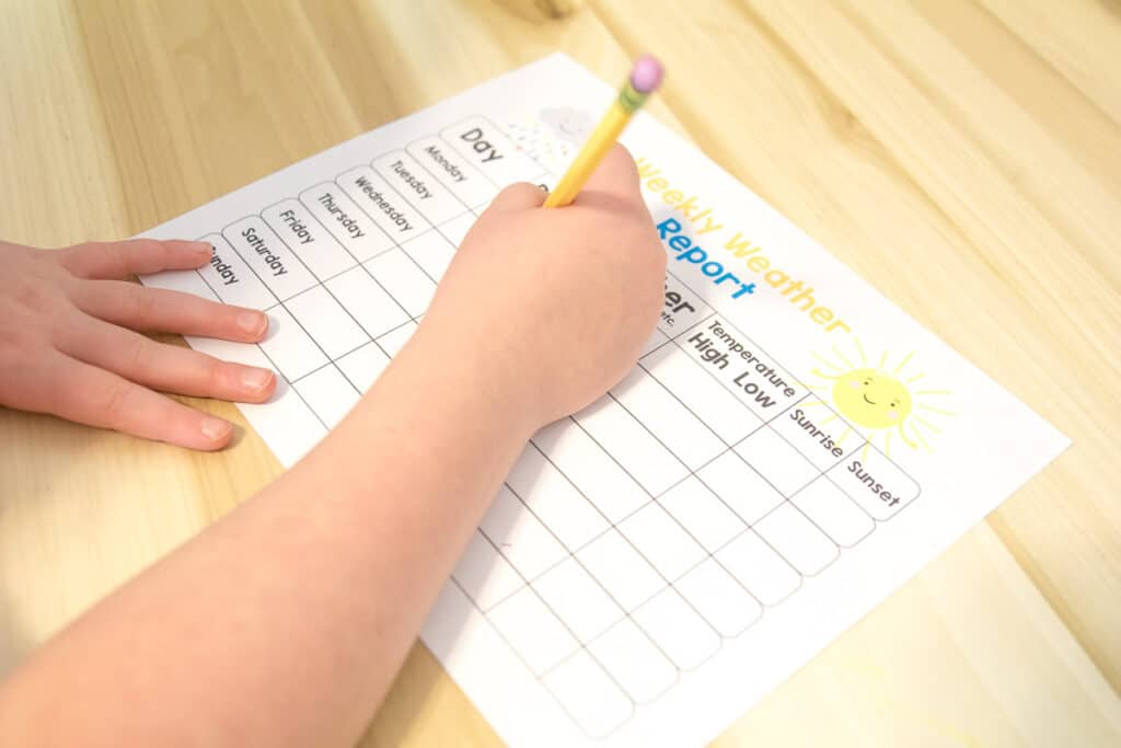Child filling out a weather chart