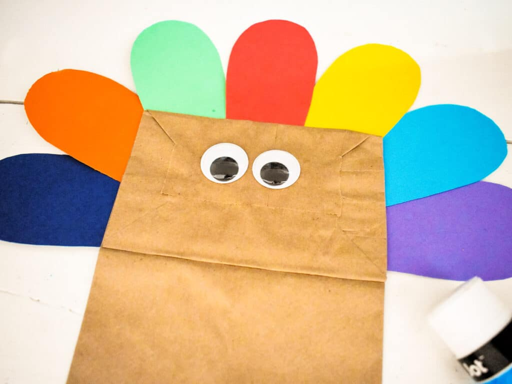 Googly eyes and feathers glued to a paper bag
