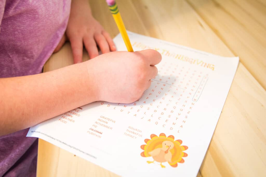 Girl working on Thanksgiving Word Find on a wooden background
