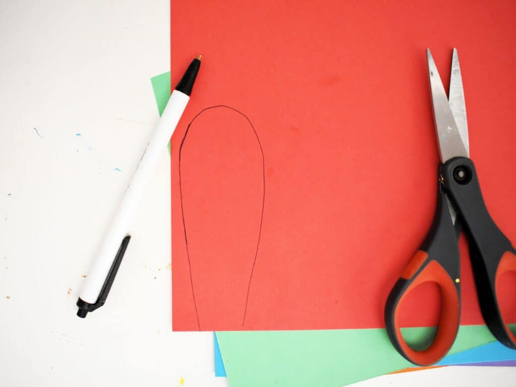 Tracing a feather on red cardstock