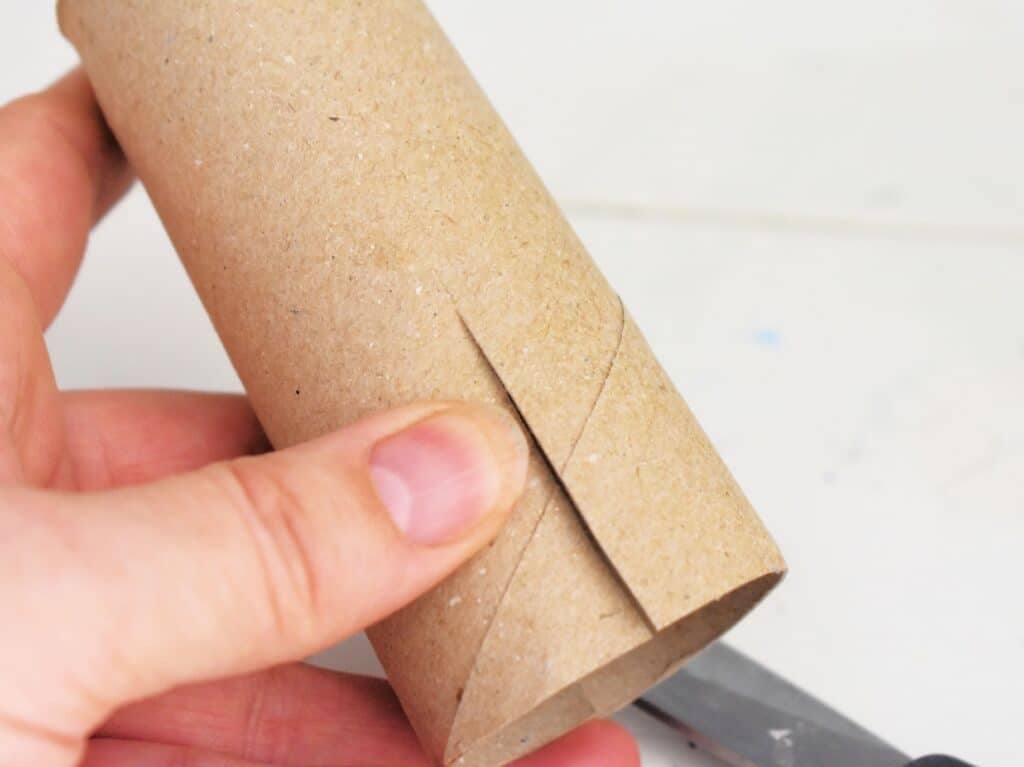 Cutting a slit in a toilet paper roll