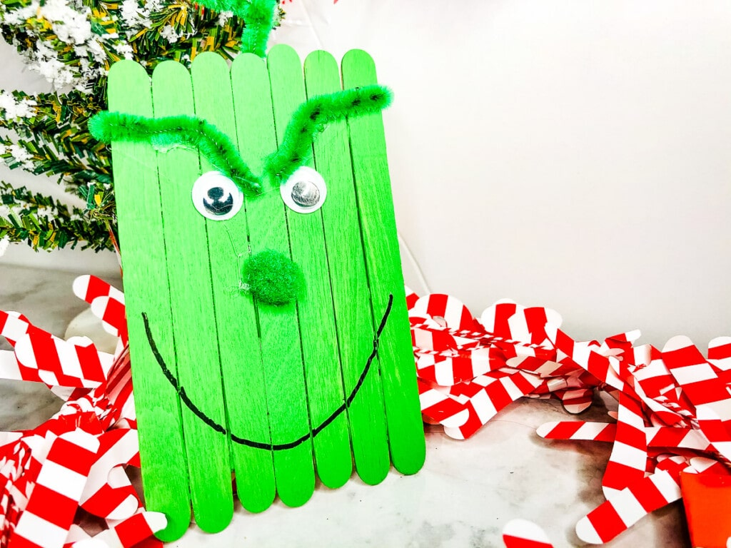 Easy Grinch Popsicle Stick Craft sitting with red and white ribbon