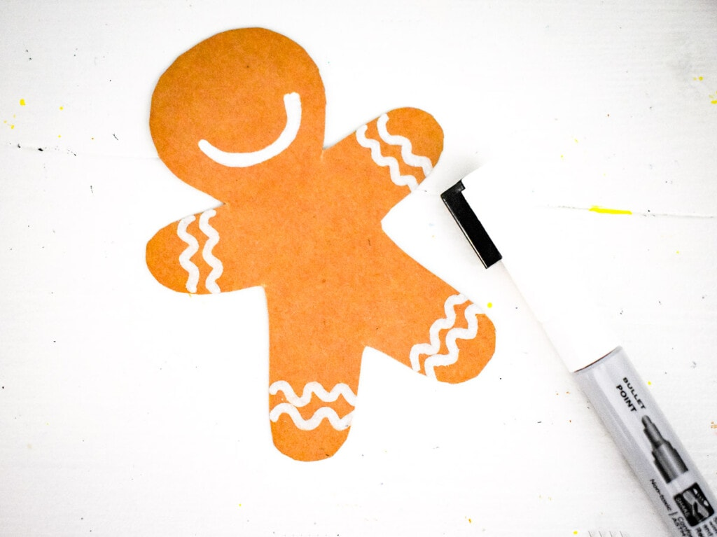 Brown gingerbread man cut out being decorated with white marker