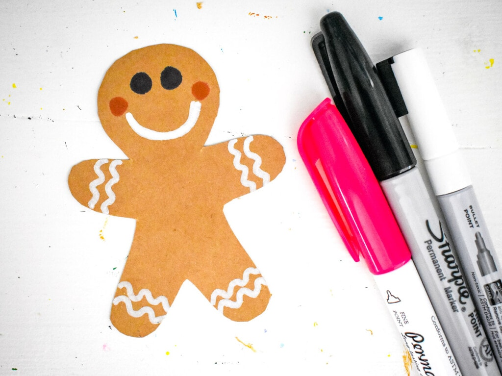 Gingerbread man cut out being decorated with marker