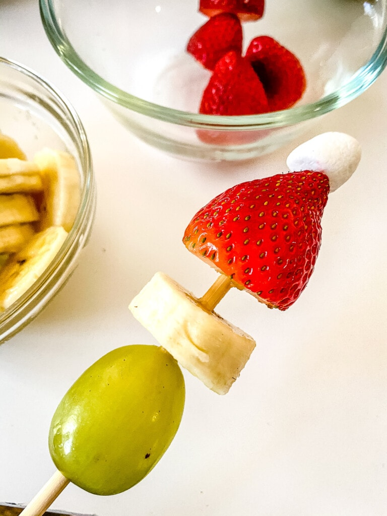 Skewer with grape, banana, strawberry and miniature marshmallow being threaded on