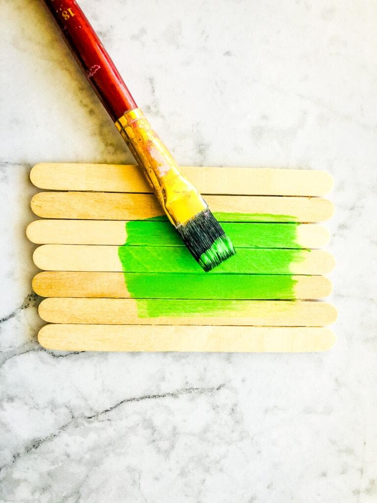 Paint brush painting popsicle sticks