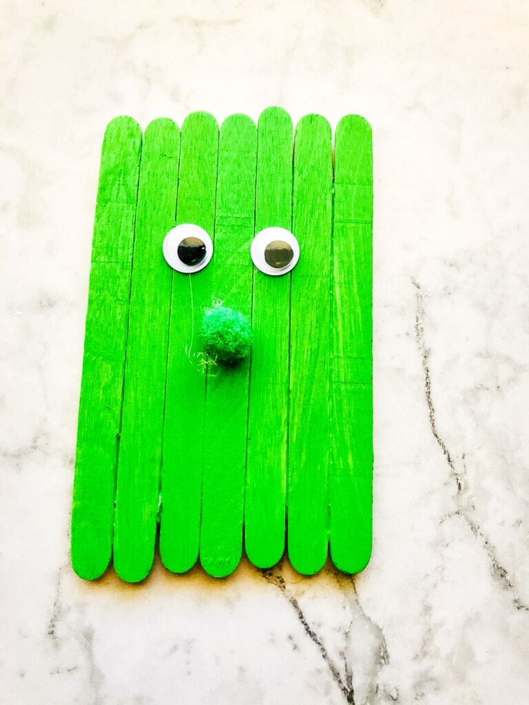 Green Popsicle sticks with nose and eyes