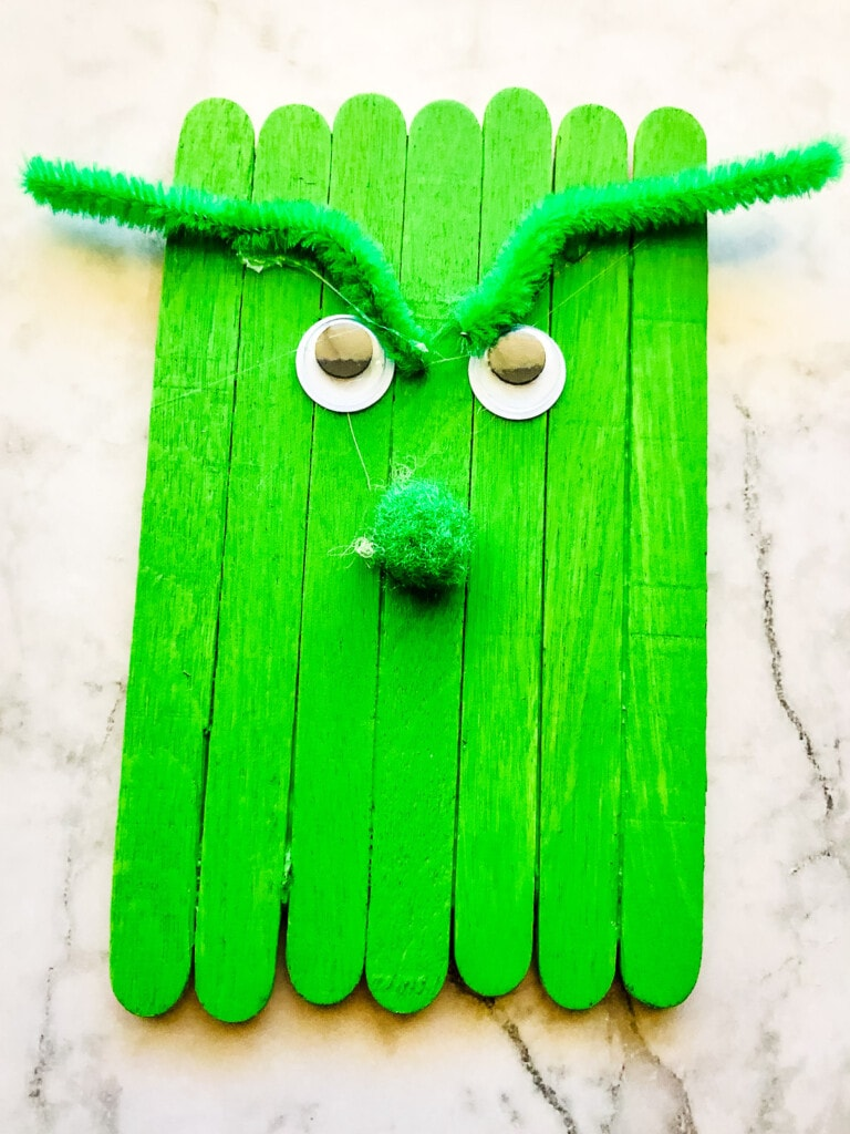Green Popsicle sticks with nose and eyes and green eyebrows