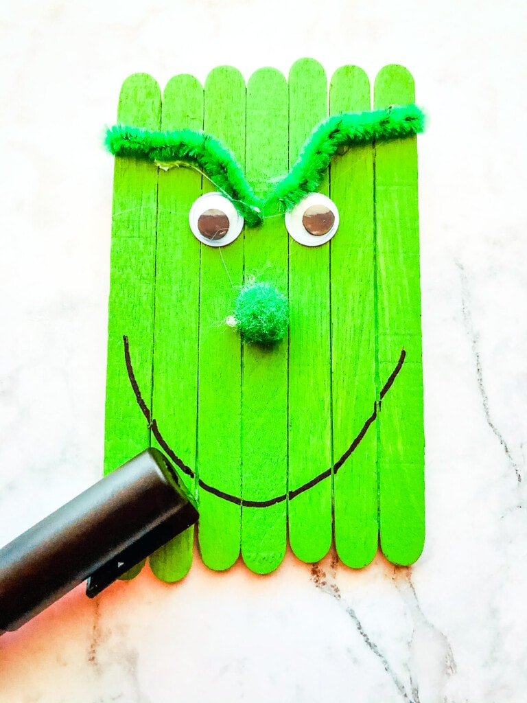 Marker writing smile on grinch popsicle stick craft
