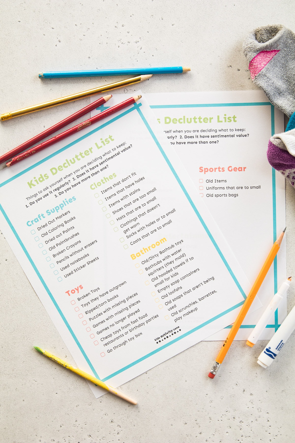Kids Declutter Checklist on light background with old markers, pencils and socks
