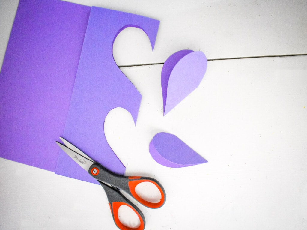 Cutting heart shapes out of purple paper