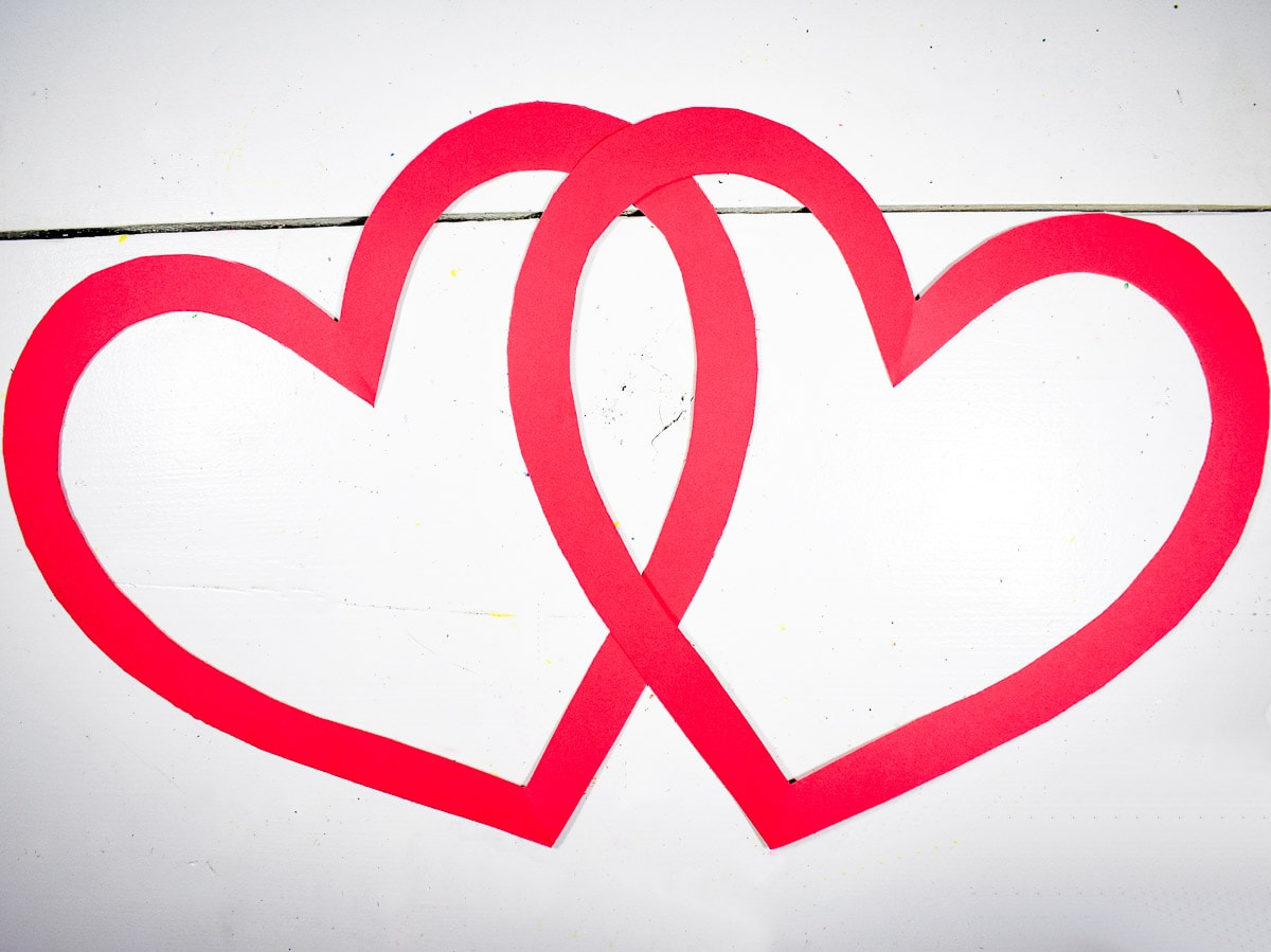 Two heart outlines in red paper overlapping