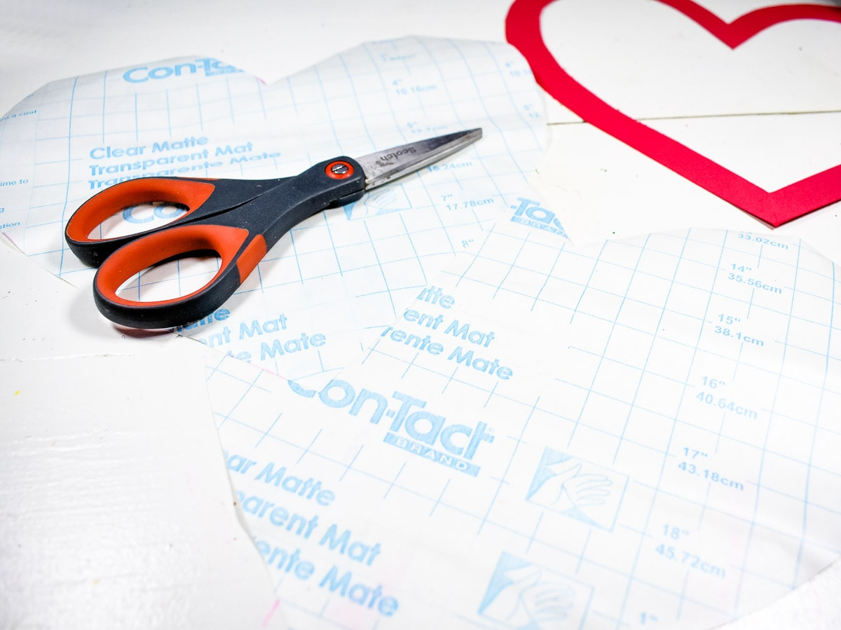 Scissors laying on a heart shaped piece of contact paper