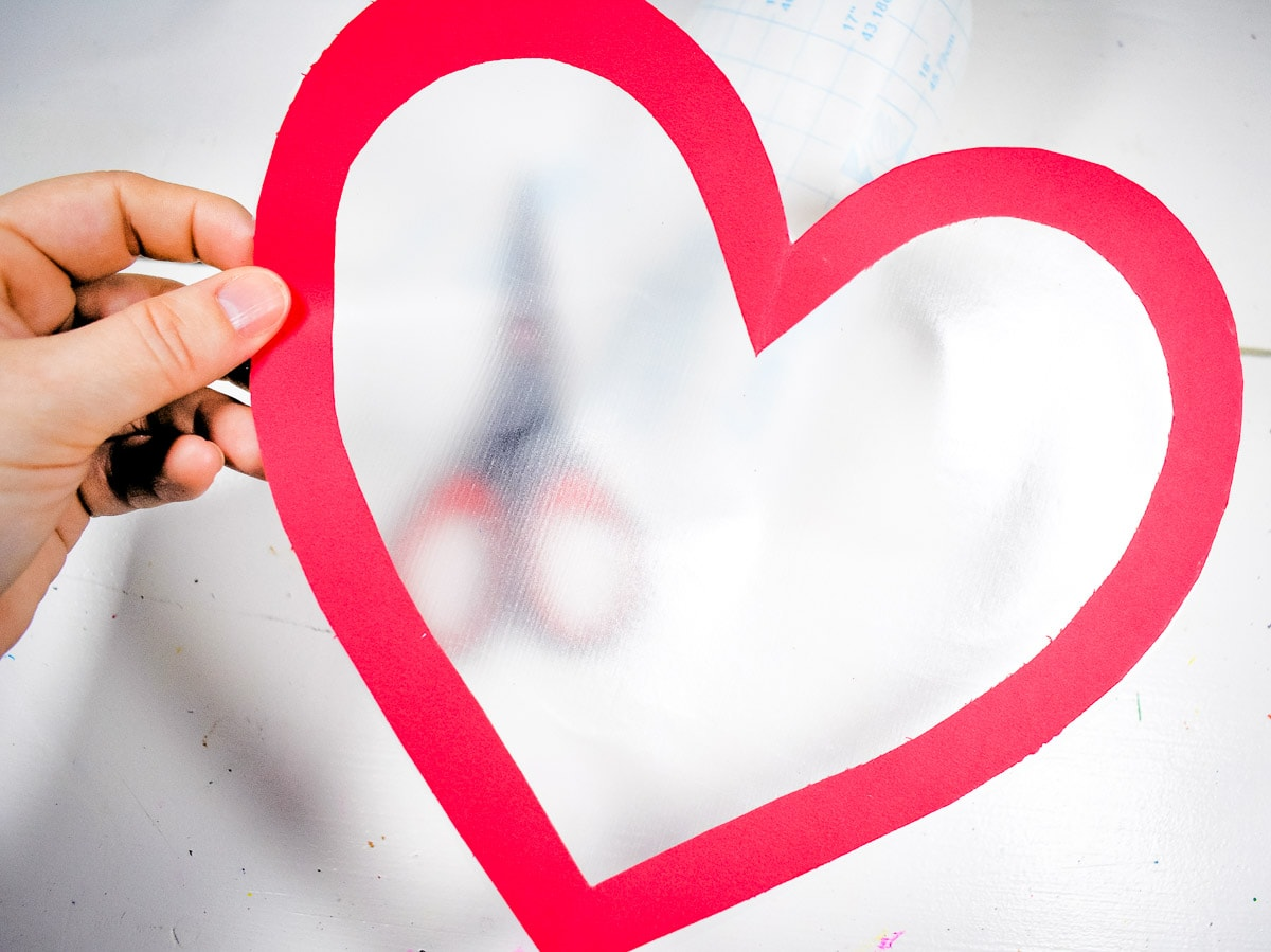 Hand holding up an outline of a heart with contact paper applied to one side.