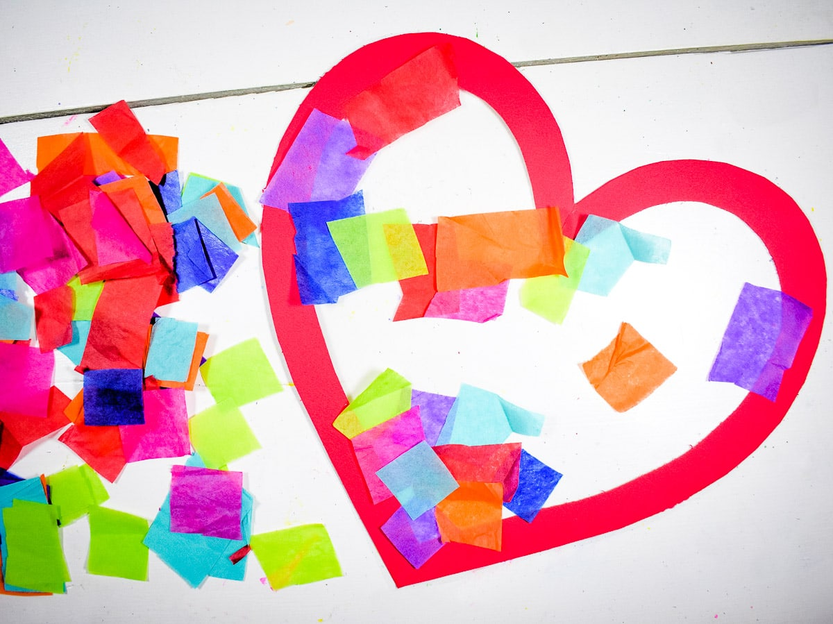 Applying squares of tissue paper to contact paper stuck to a heart