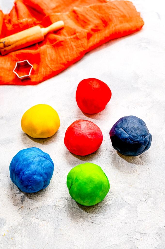 Balls of colored homemade playdough on light background