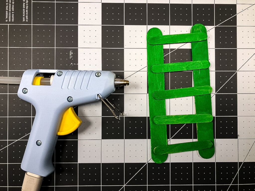 Making a green ladder out of popsicle sticks
