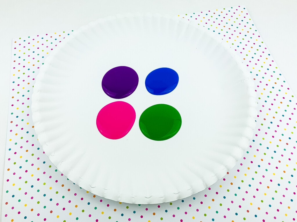 White paper plate with four different colors of paint