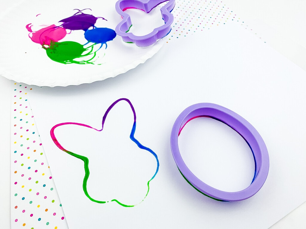 A colorful outline of a bunny head from paint on cookie cutter