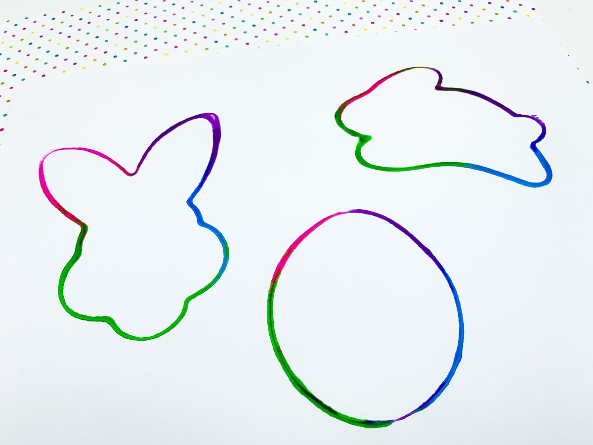 Colorful outlines of Easter images from cookie cutters dipped in paint