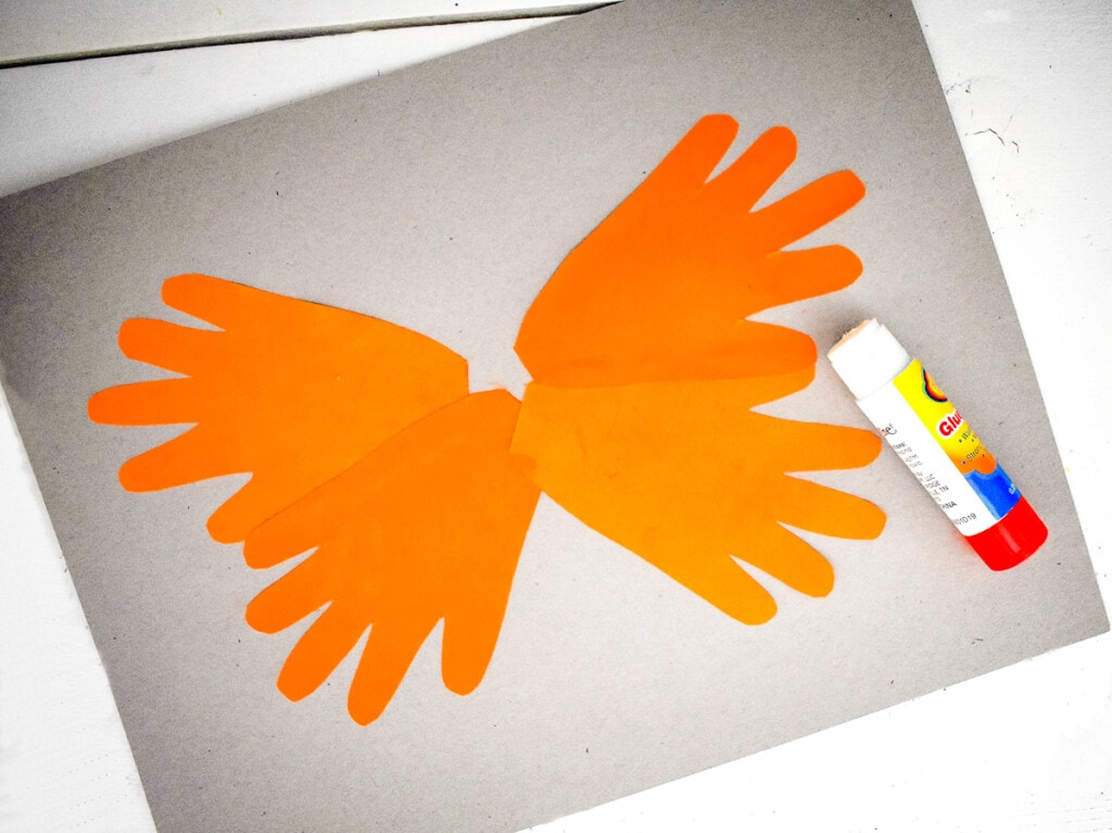 Arranging handprint cut outs to make butterfly shape