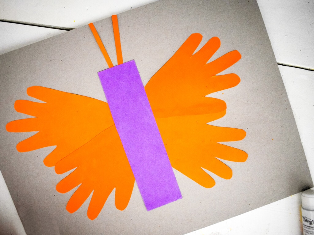 Assembling butterfly out of handprints on paper