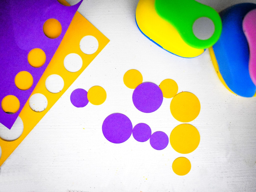 Punching yellow and purple circles out of paper