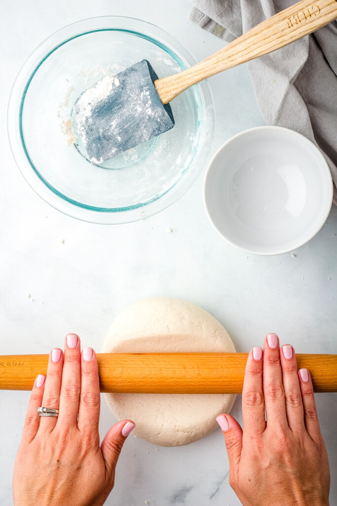 Hands rolling salt dough out with rolling pin