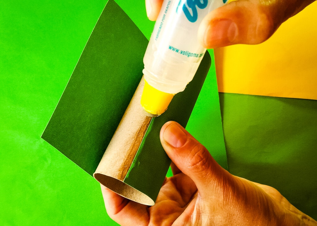 Gluing green paper to toilet paper roll