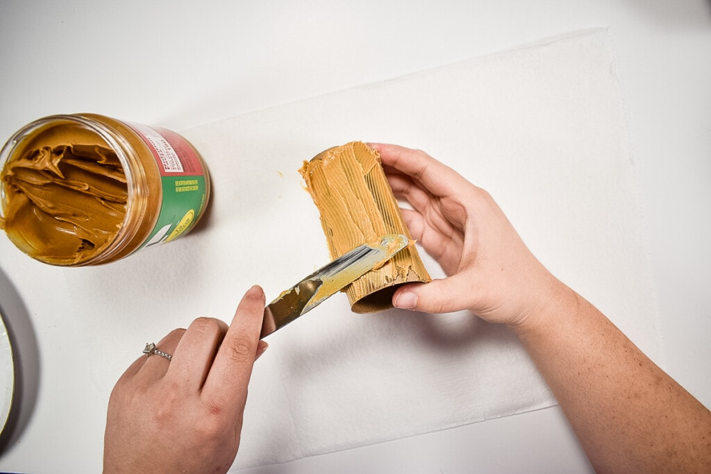 Knife spreading peanut butter over toilet paper roll
