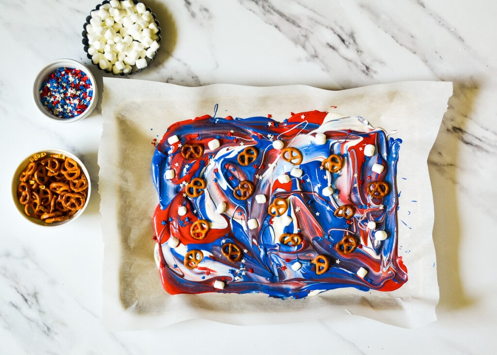 Pretzels and marshmallows on top of swirled red white and blue candy melts