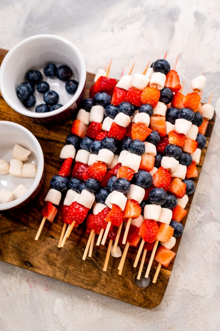 Red White and Blue Fruit Skewers on a wooden cutting board