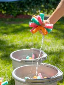 Hand squeezing a reusable sponge water bomb