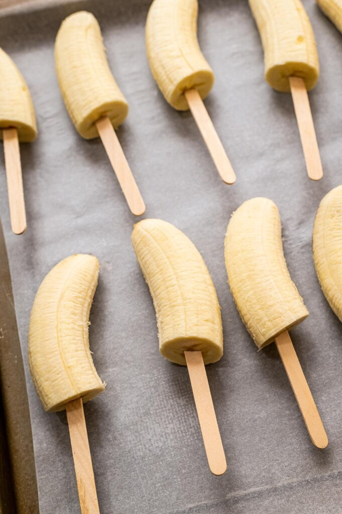 Half of bananas with popsicle sticks in them
