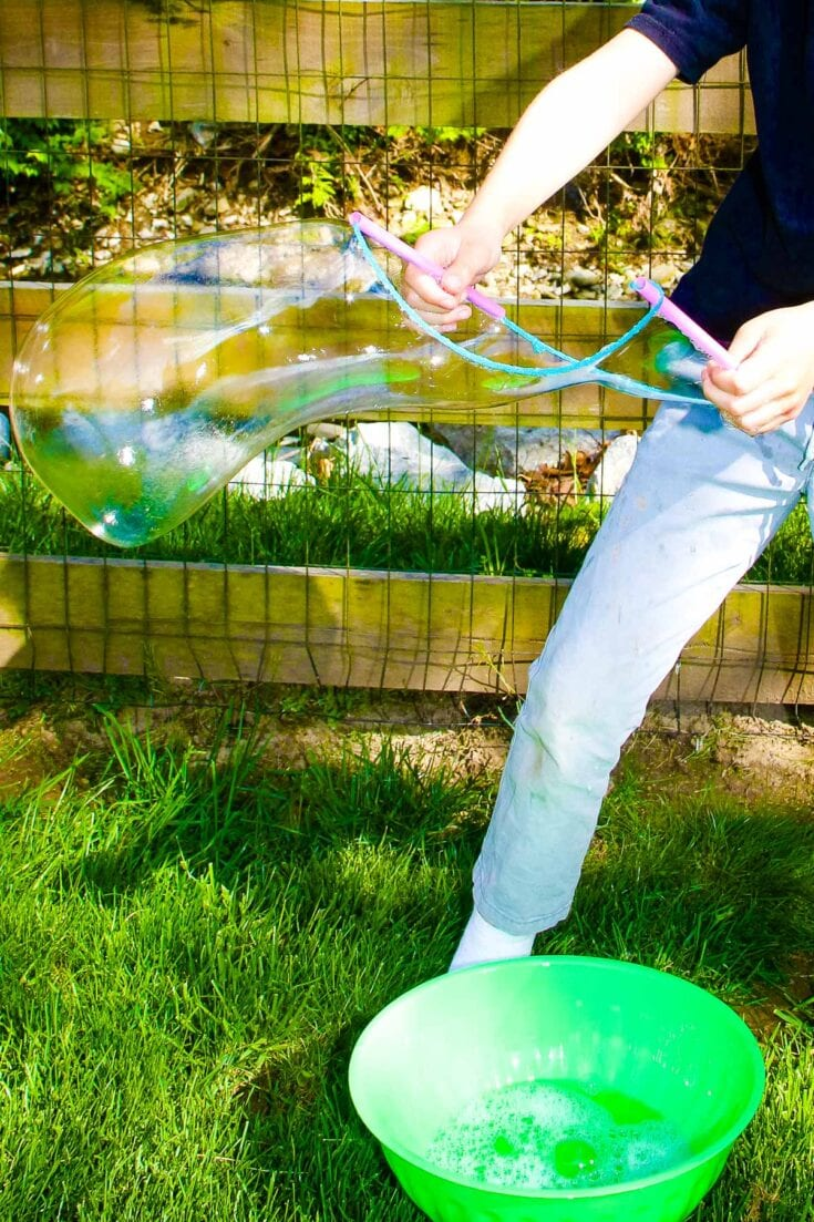 Child making huge bubble with homemade bubble wand