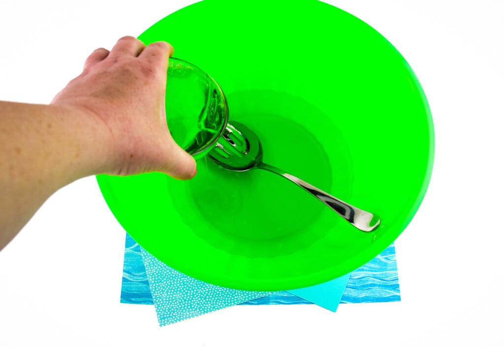 Pouring mixture in green bowl for bubbles