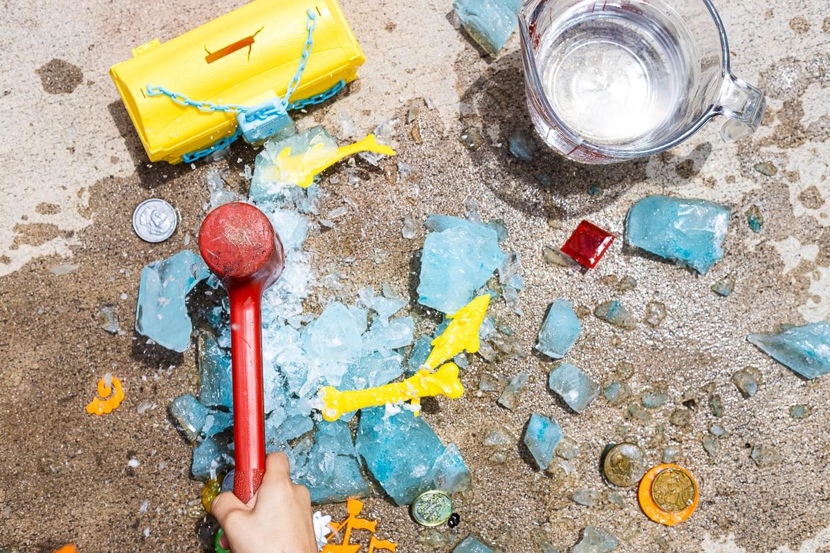 Red hammer breaking apart ice block treasure hunt