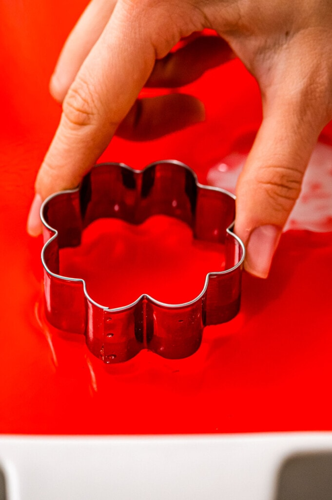 Hand using cookie cutter to cut out a Jell-O Jiggler