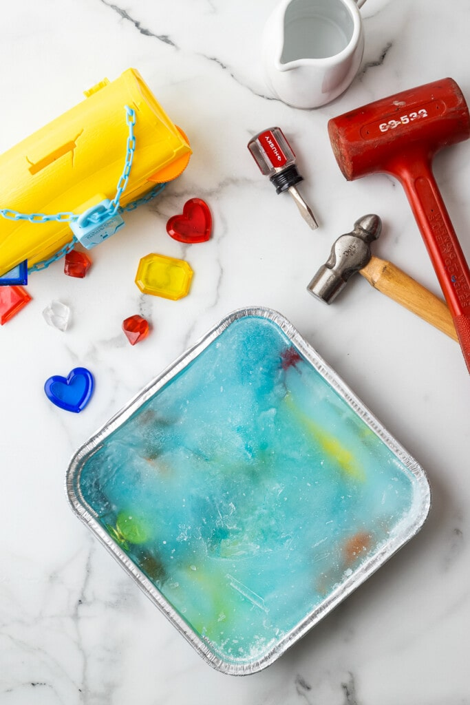 Square aluminum foil pan with frozen water and plastic toys