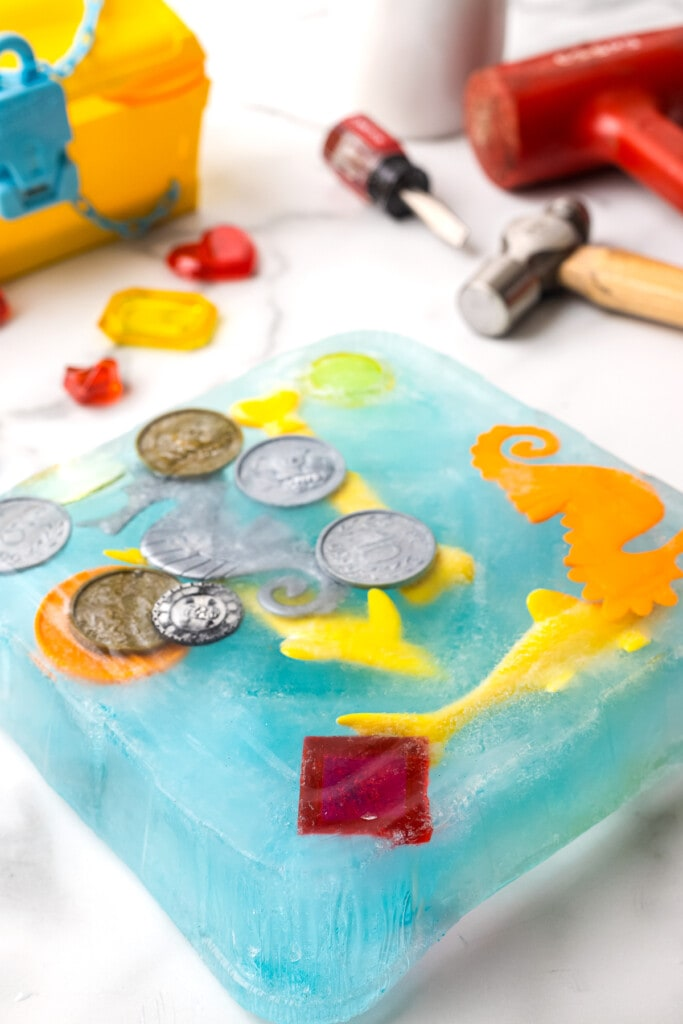 Square block of blue ice with plastic toys