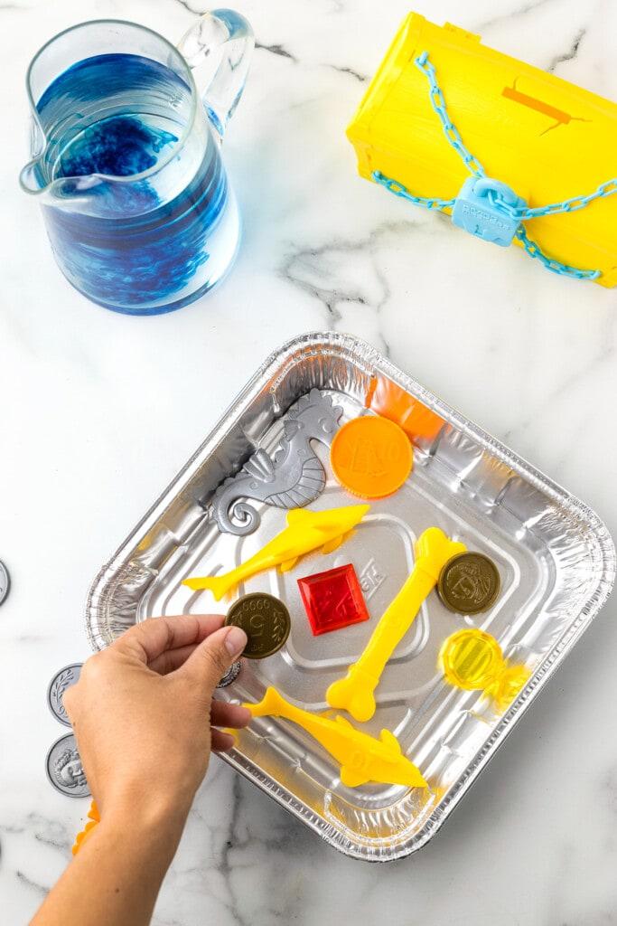 Hand putting plastic toys into a square aluminum foil pan