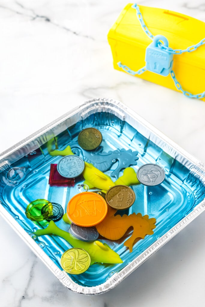 Square Aluminum Foil pan with blue water and plastic toys.