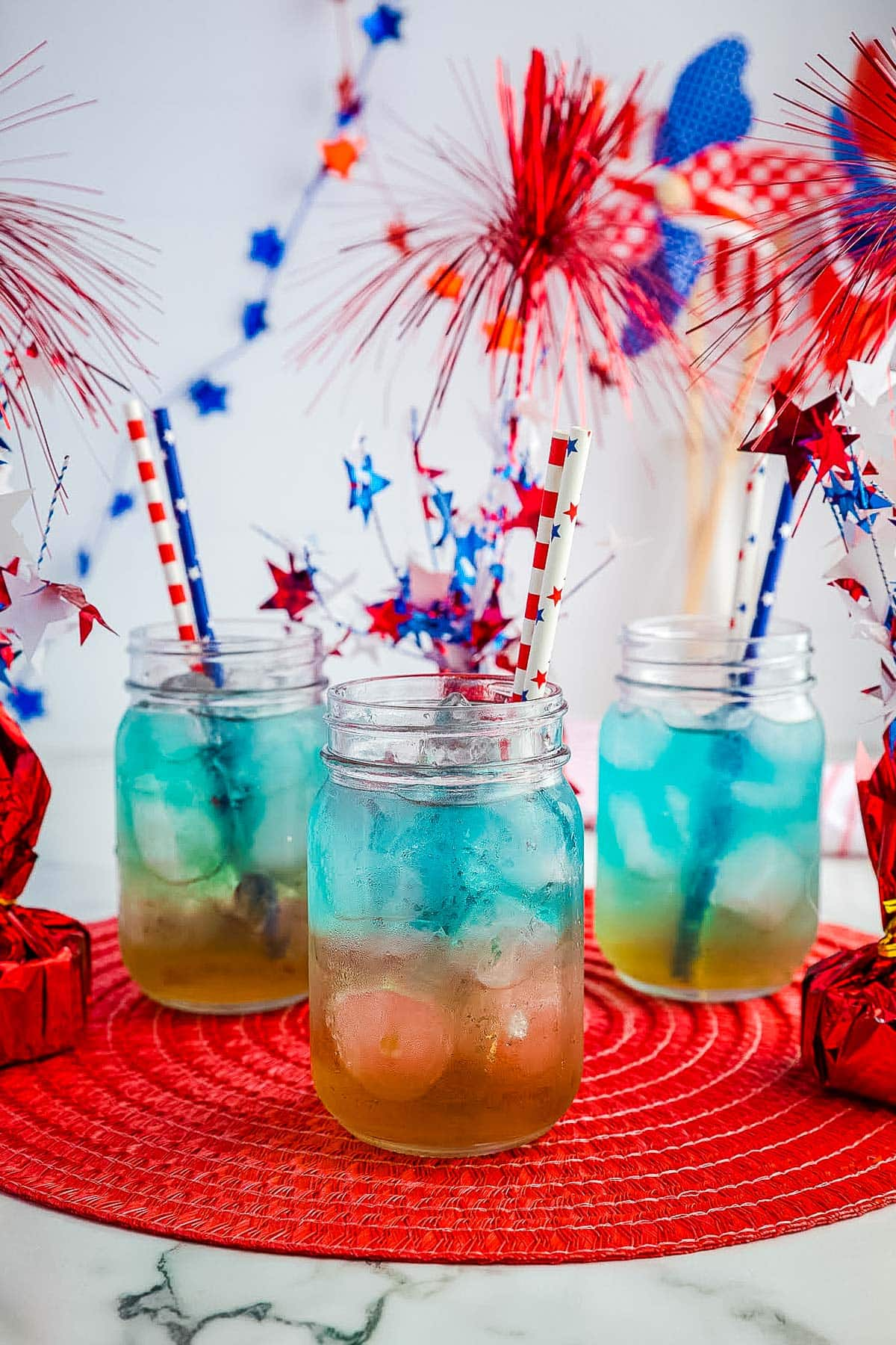 Red White and Blue Punch in three mason jars with red, white and blue decor