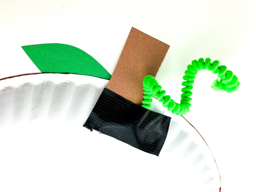 Green curly pipe cleaner taped to plate