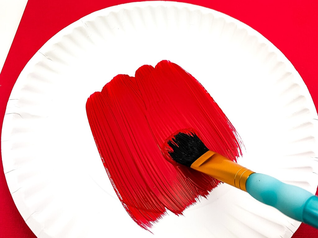 White paper plate being painted red