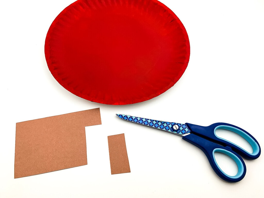 Scissors with brown paper and red paper plate