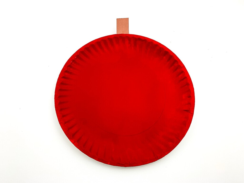 Paper plate painted red with brown paper stem attached to top