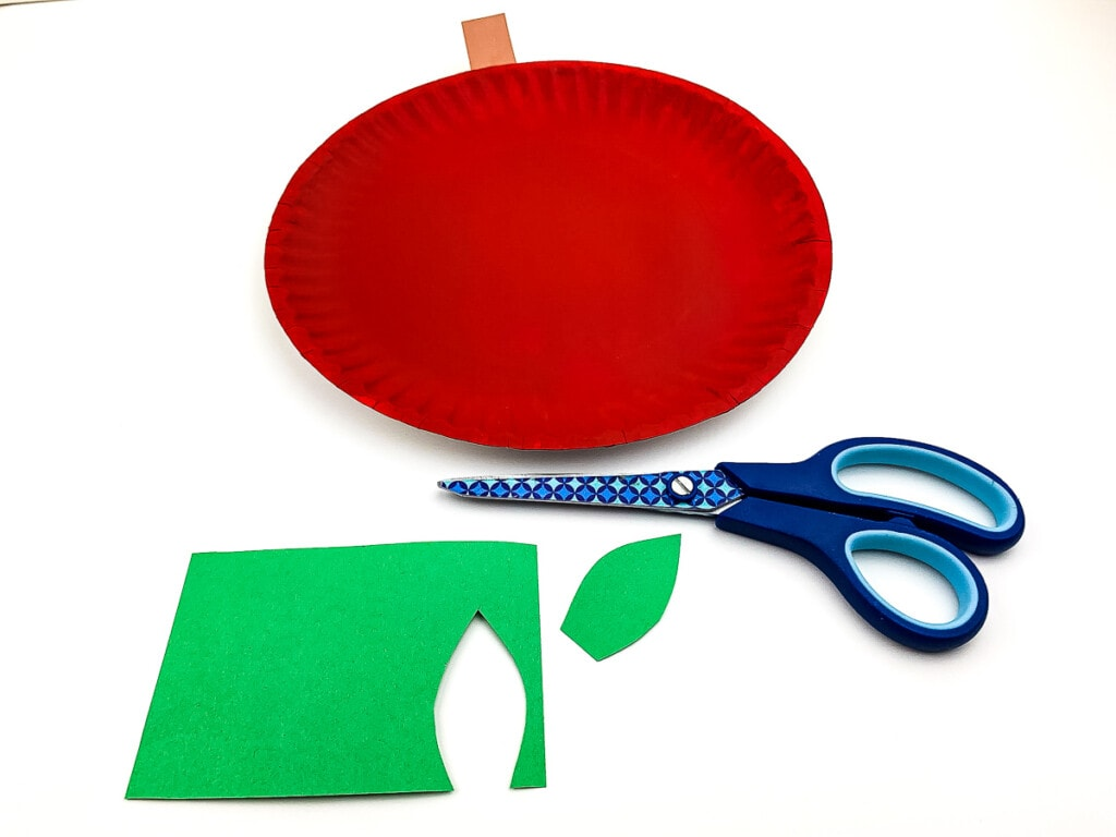 Green paper stem cut out laying with scissors and red paper plate